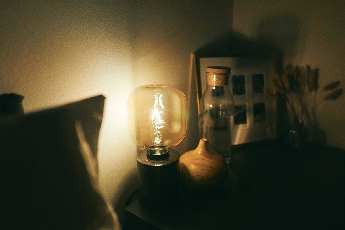 A bedside table lamp is on at night.