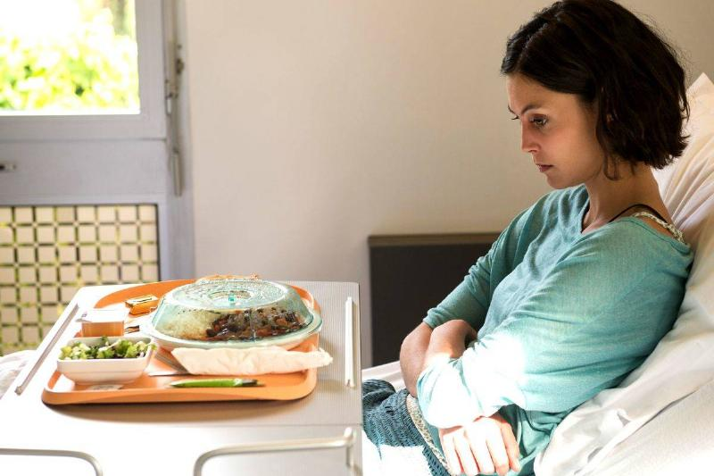 A woman refuses to eat a meal that is on her tray.