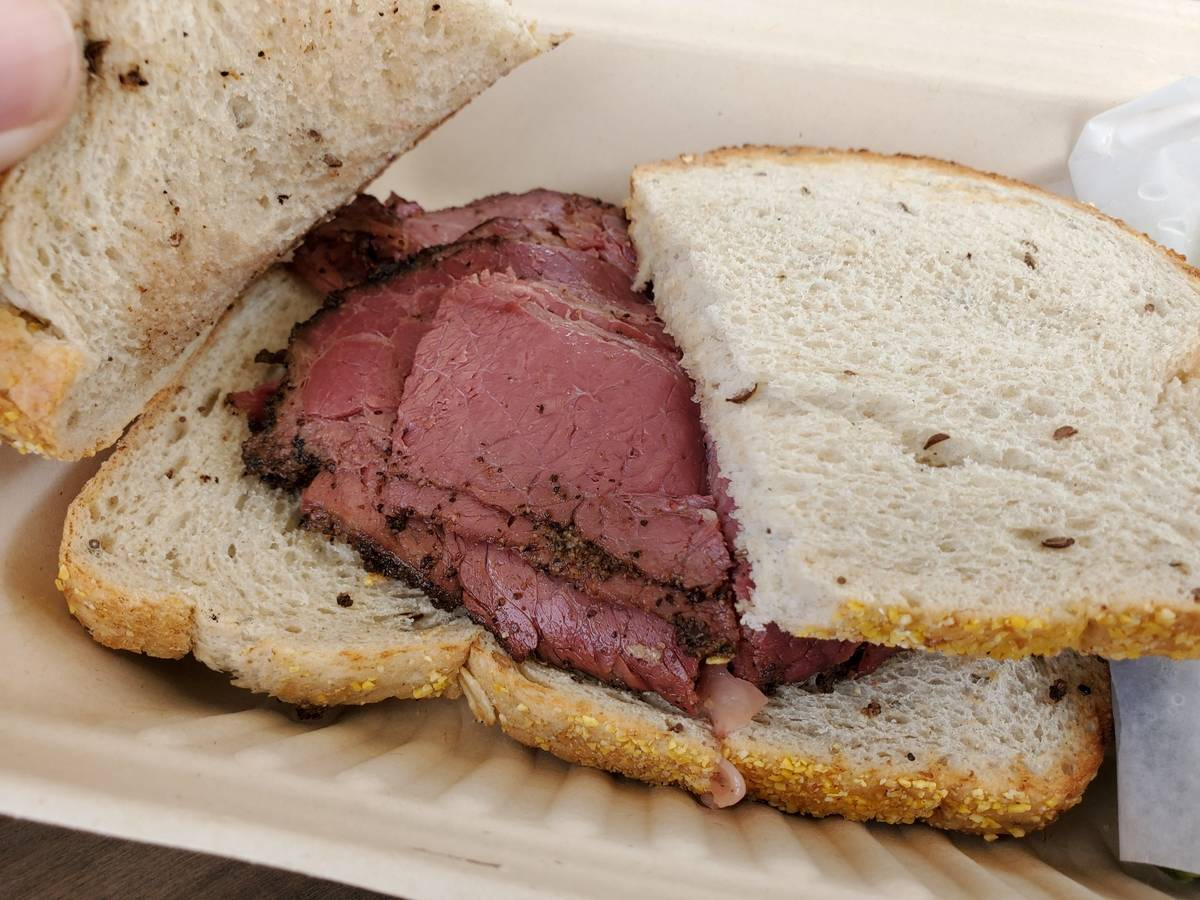 A person removes sourdough bread to reveal slices of pastrami.