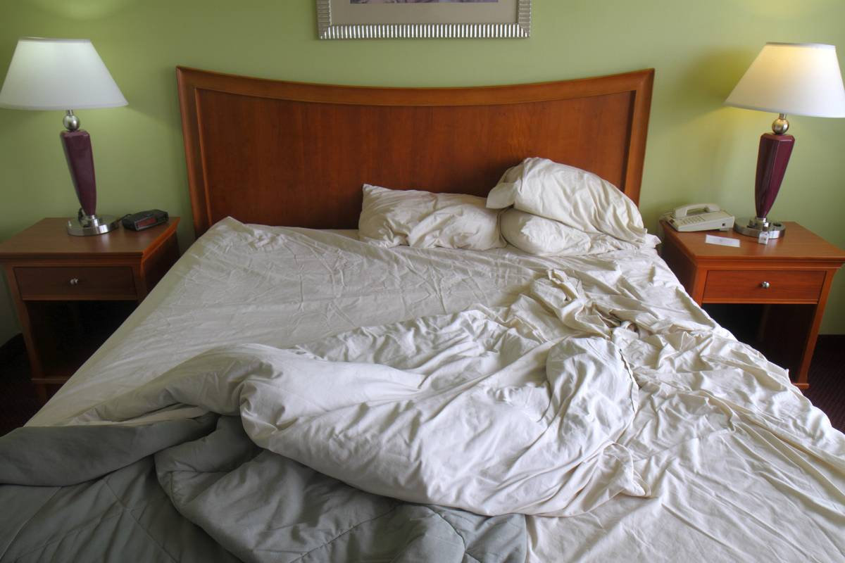 A messy, unmade bed is seen in a hotel.
