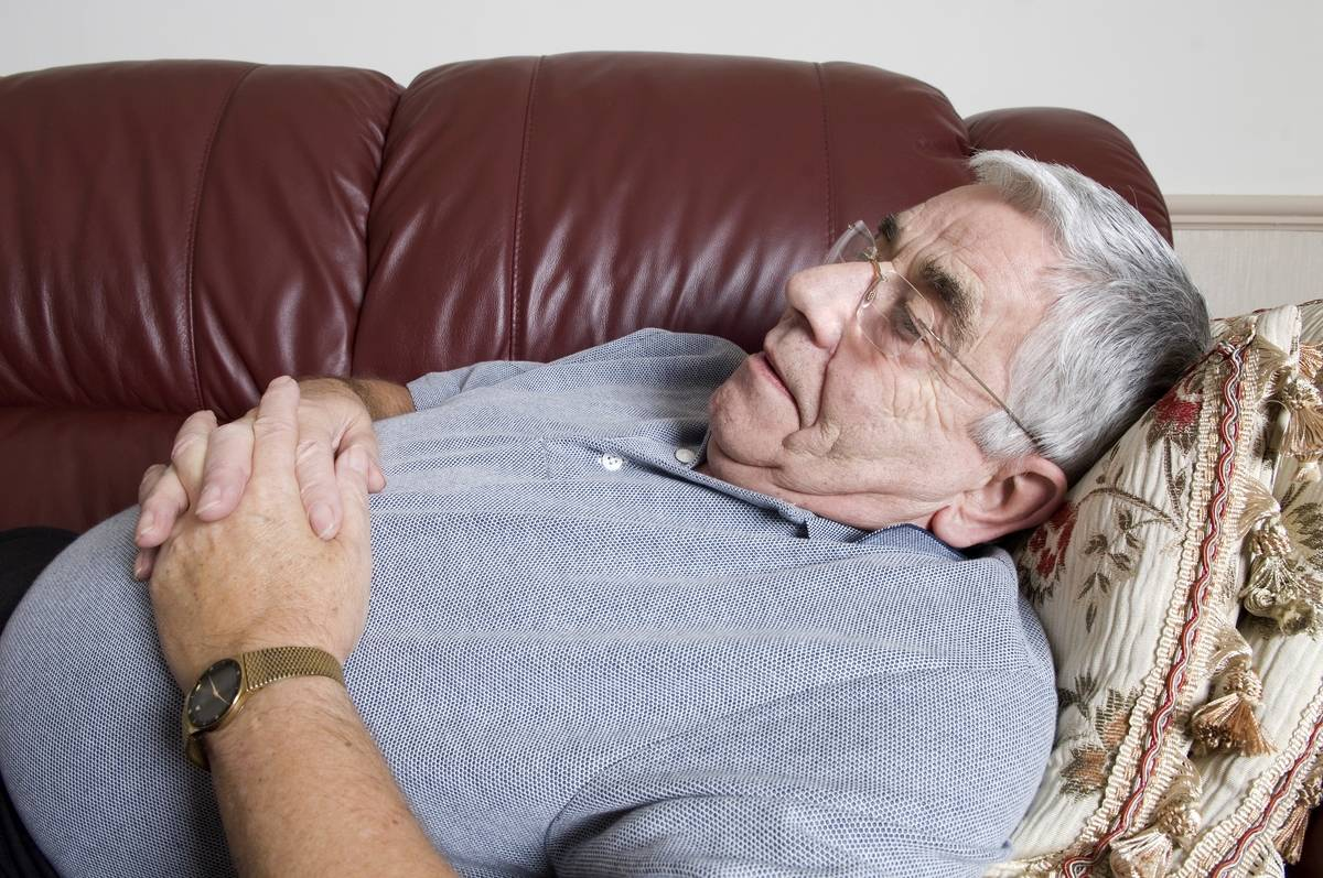 A senior man naps on his couch.
