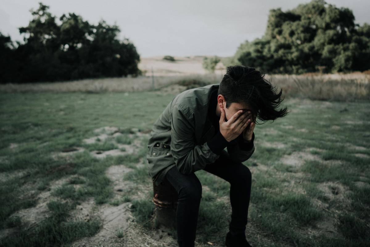 A man kneels and puts his face in his hands.