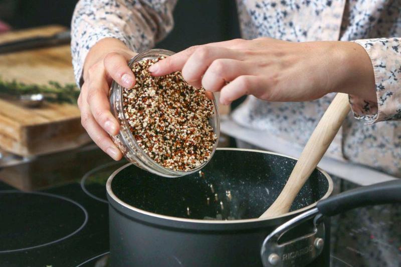 someone pouring quinoa into a pot