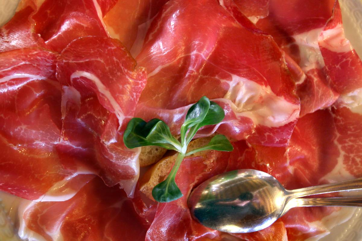 Cured red meat is seen under greens and a spoon.
