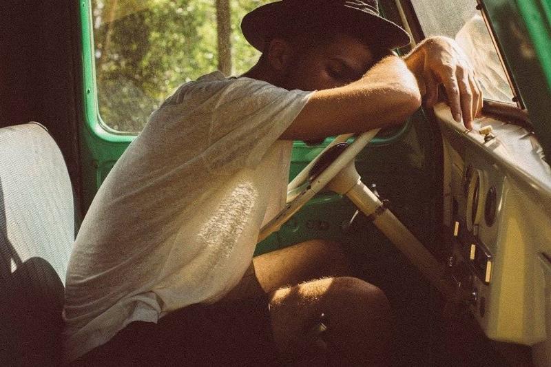 A man falls asleep on a car wheel.