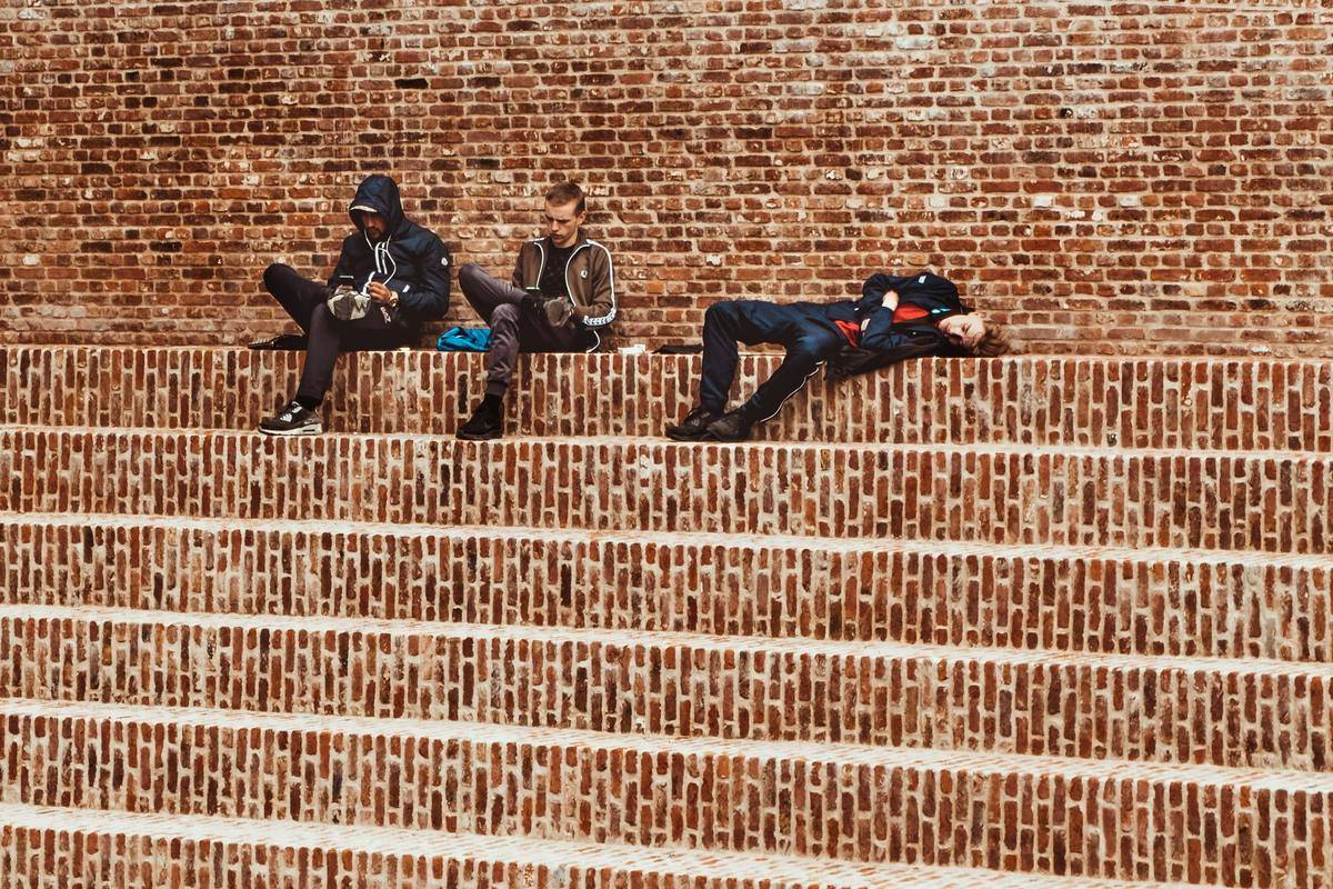 Two teenagers sit on brick steps while the third takes a nap.