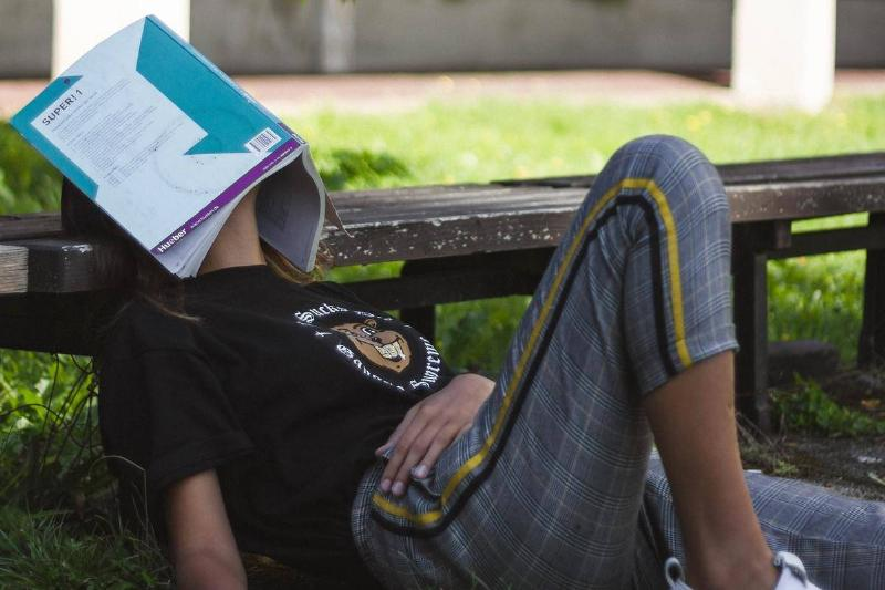 A woman sleeps outside with her book over her eyes.