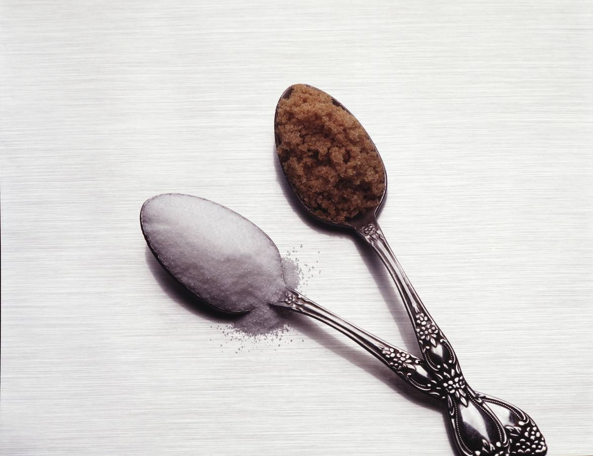 Two spoons hold white and brown sugar.