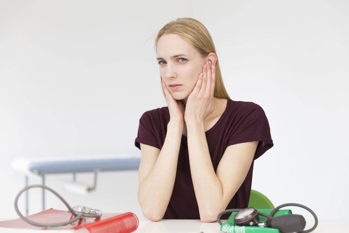A woman with tinnitus clutches her ears in pain.