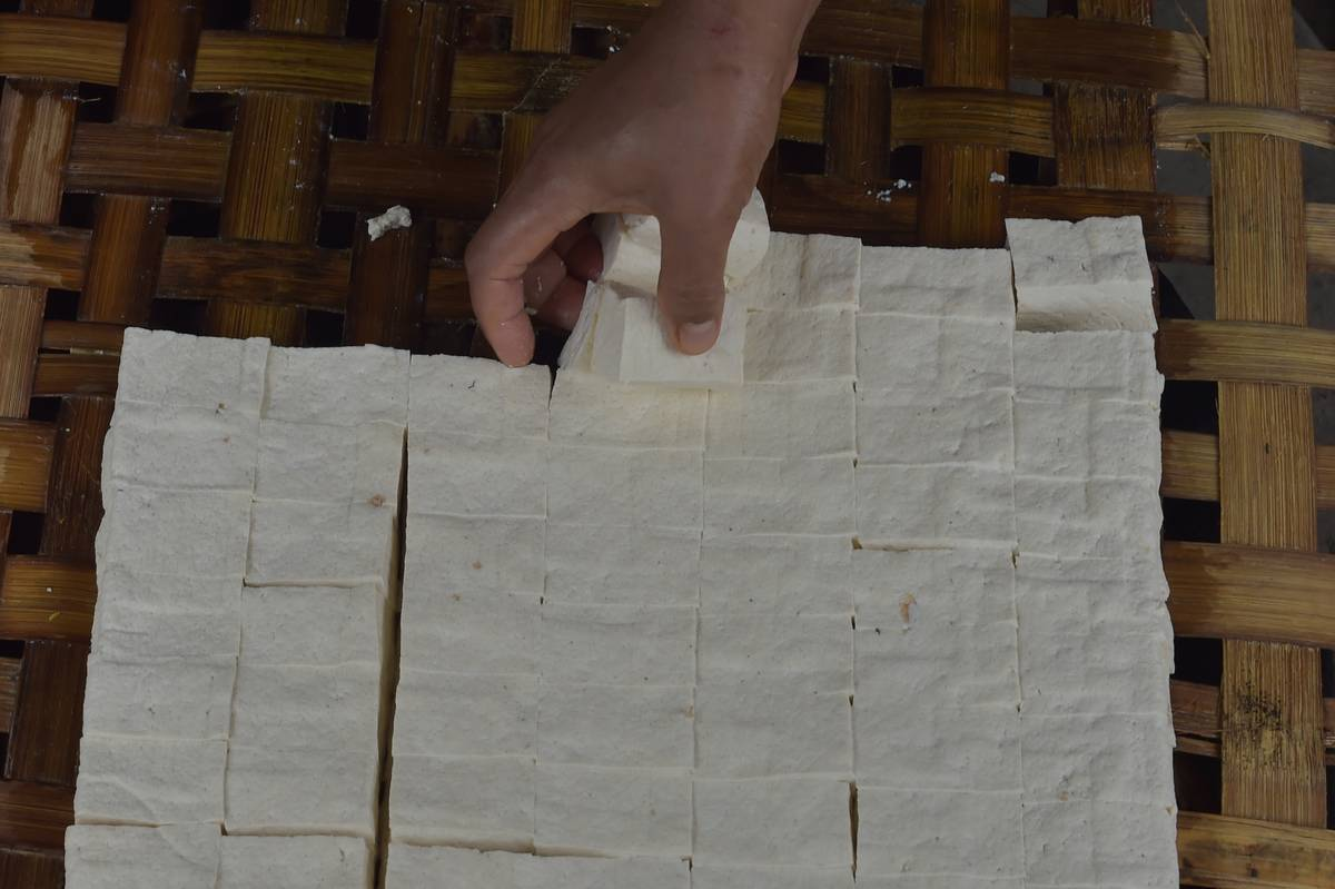 A person picks up squares of tofu.