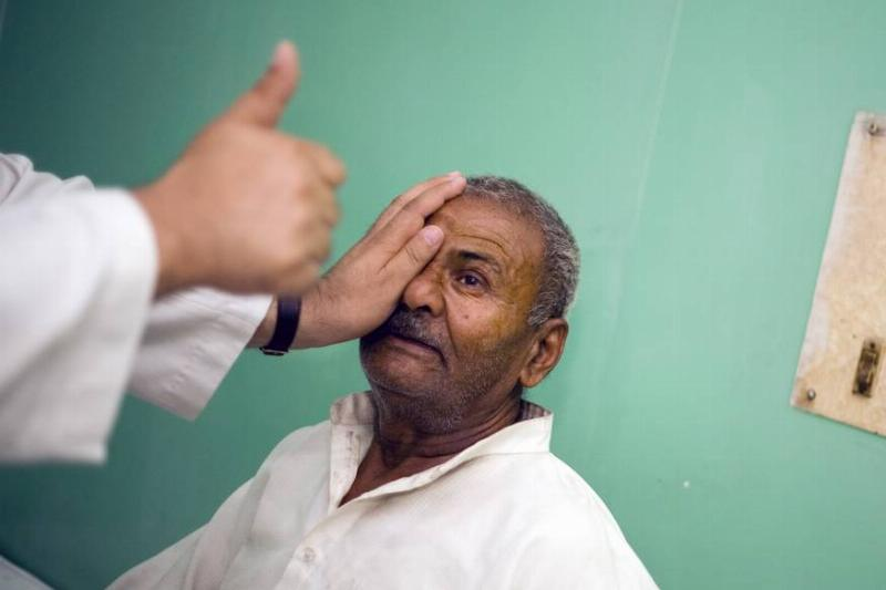 A doctor covers a patient's eye during a vision test.