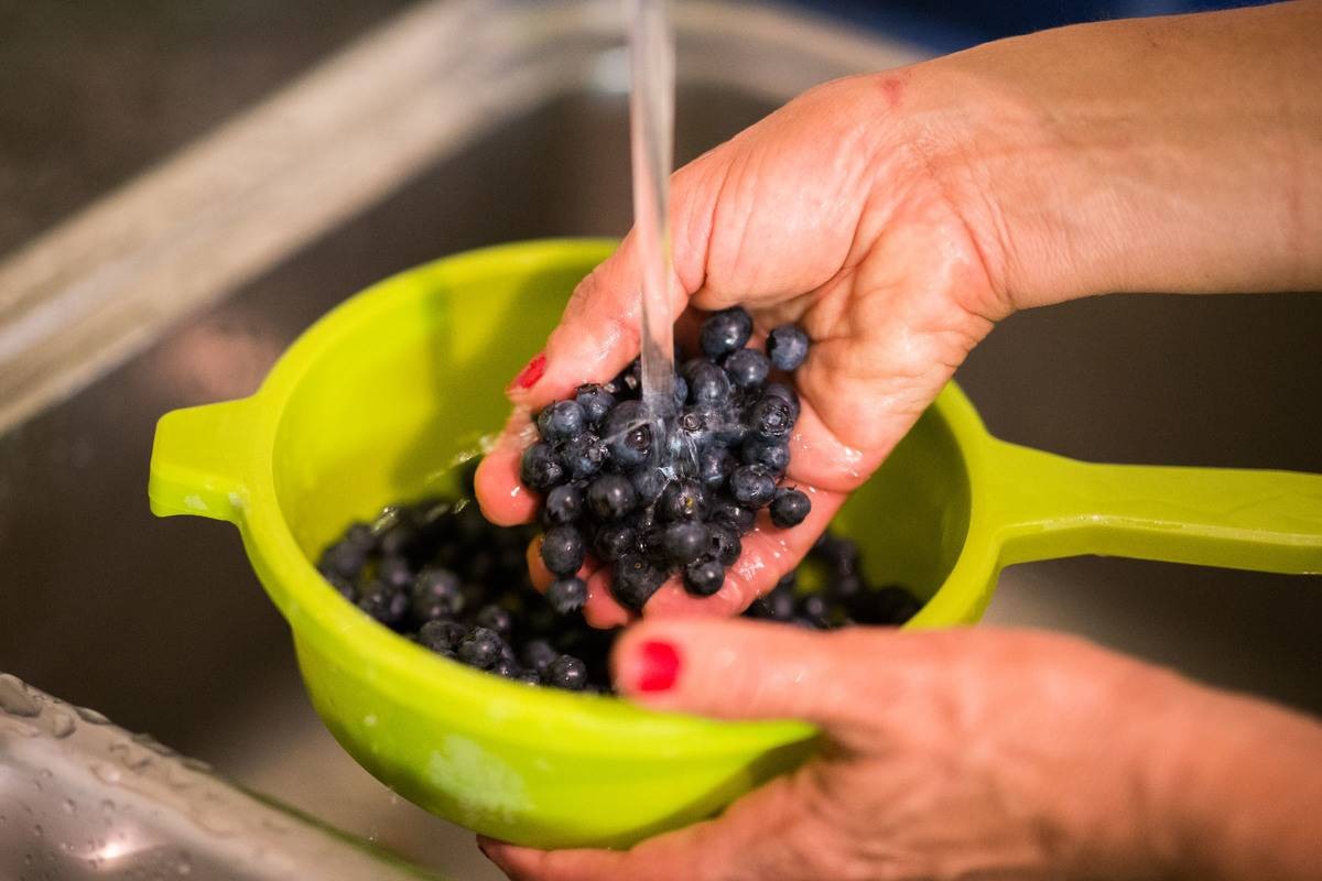 A woman washes blueberries in the sink.
