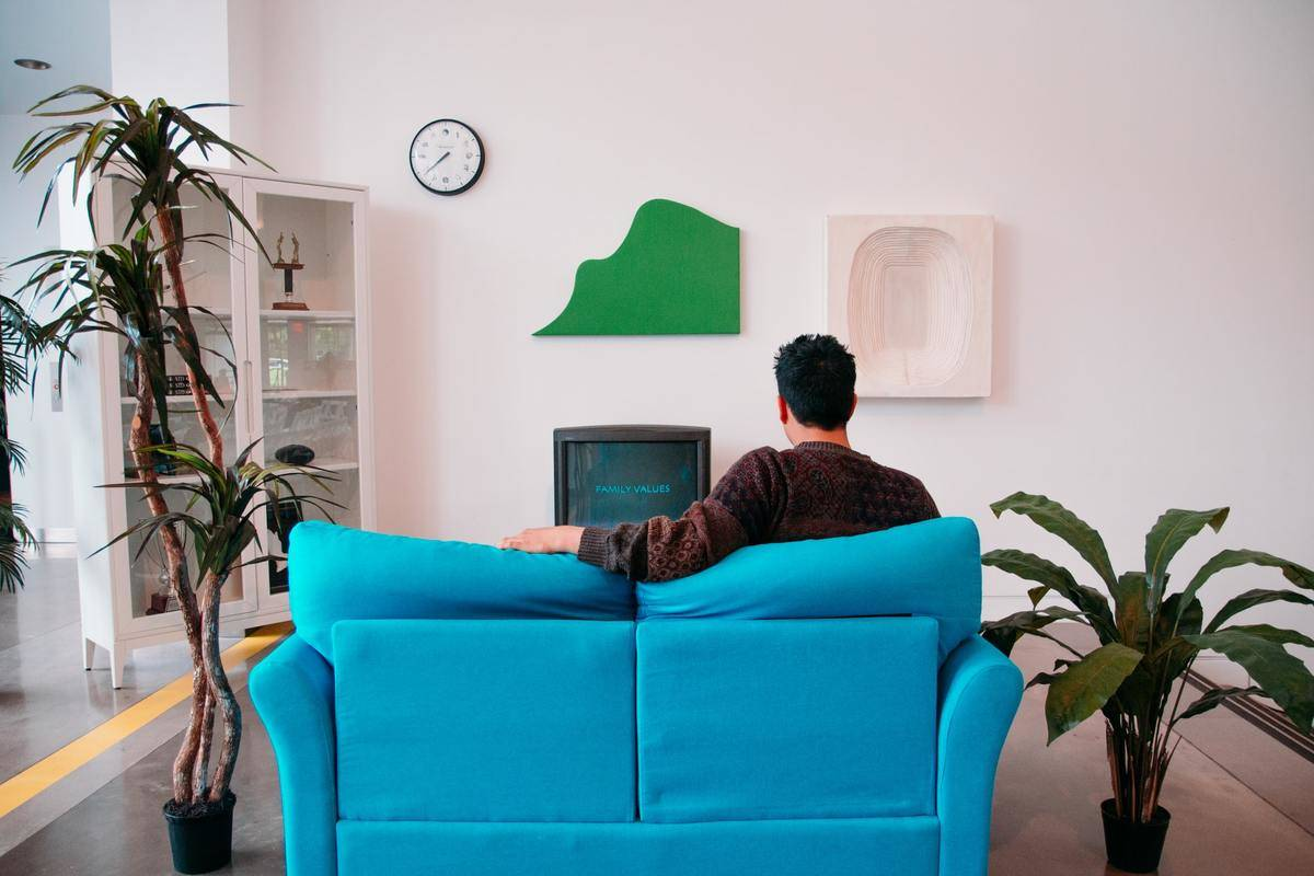 A man watches TV while sitting on a couch.