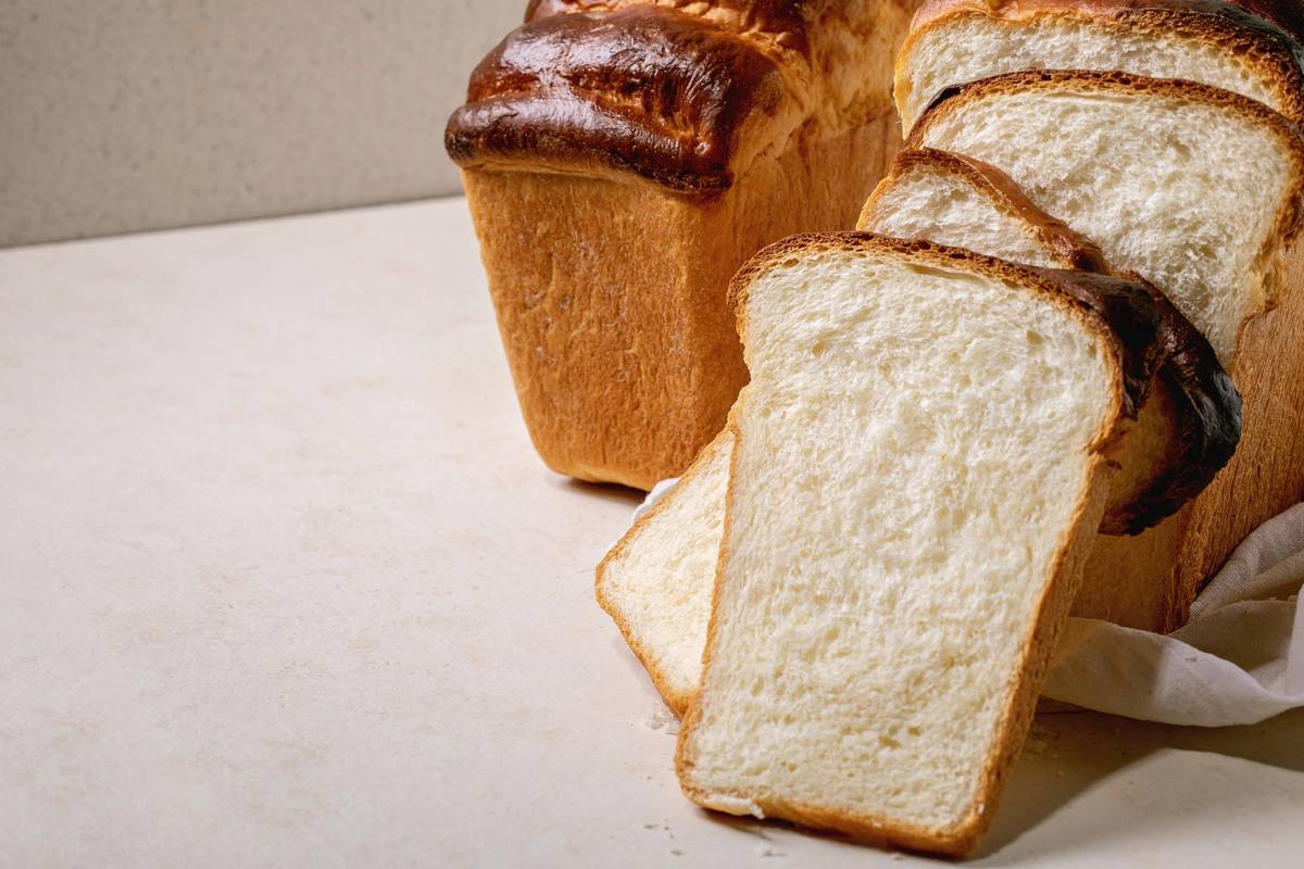 Homemade Hokkaido wheat toast bread is sliced on white cloth on table.