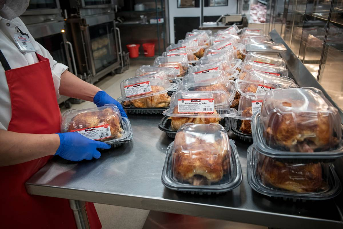 A Costco employee packages and sets out wholesale rotisserie chickens.