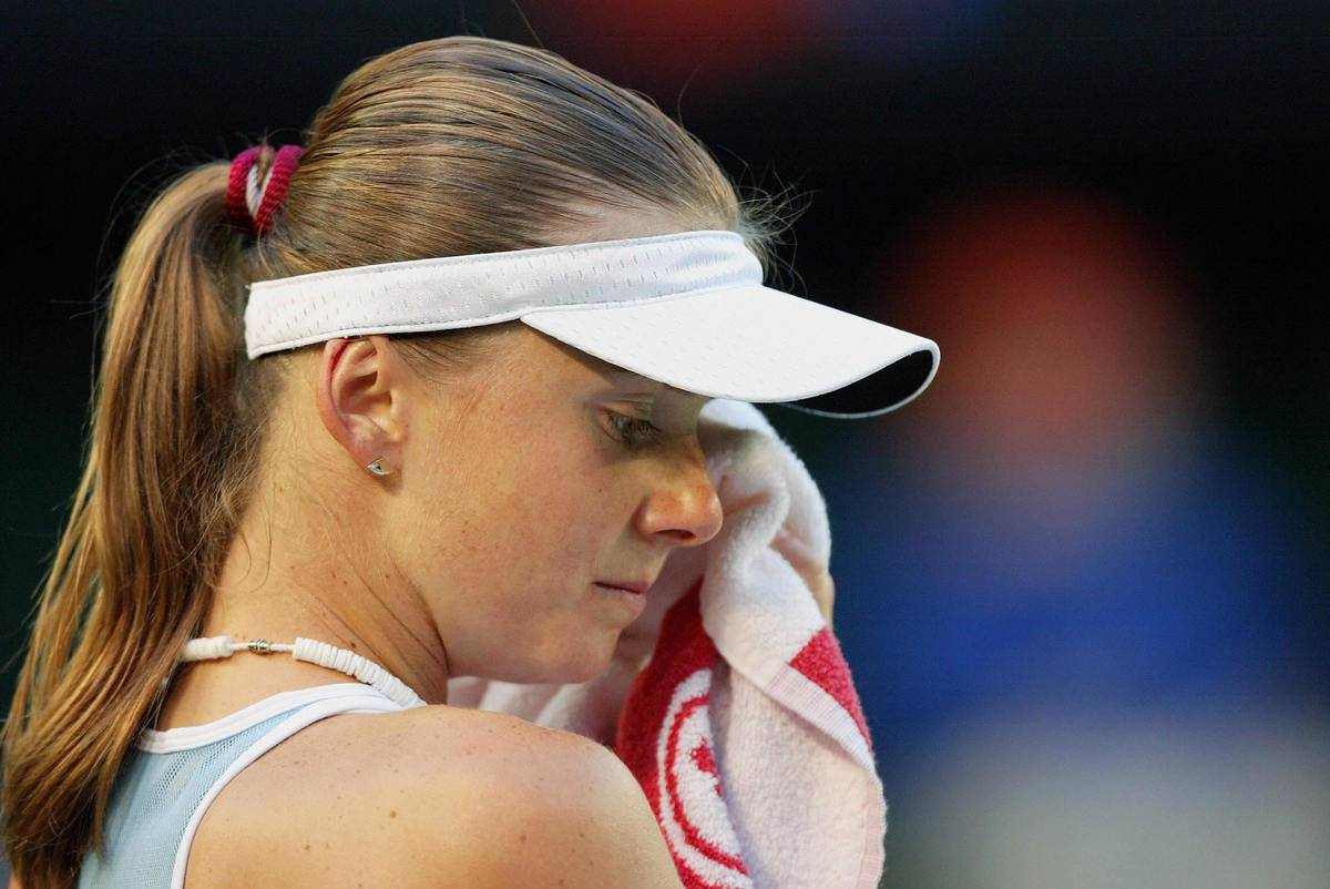 A tennis player wipes sweat off her brow.