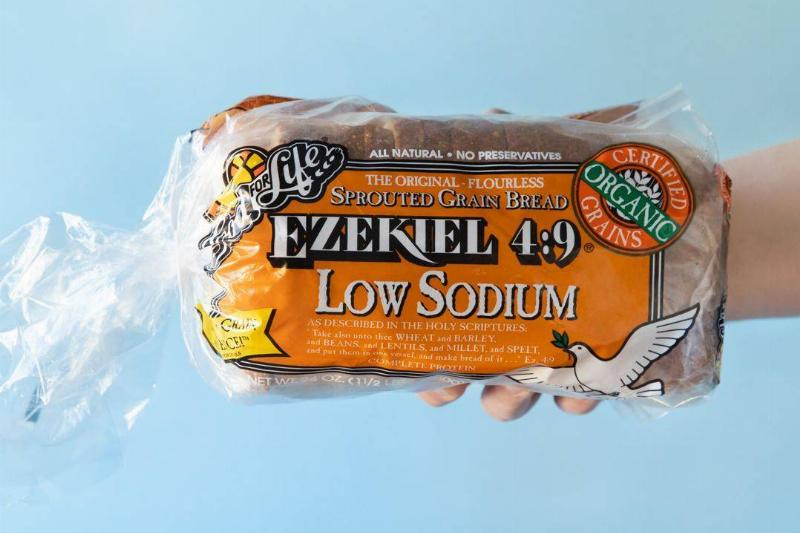 A person holds out a packaged loaf of Ezekiel Bread.
