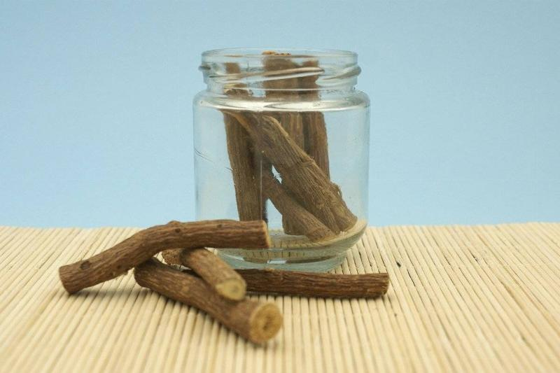 A glass jar sitting on a mat holds licorice root.
