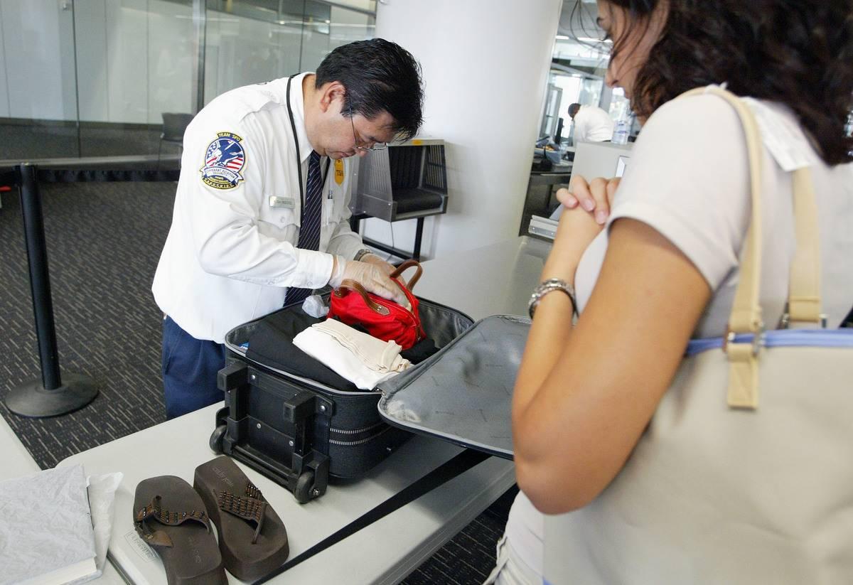 A TSA member searches through a passenger's luggage.