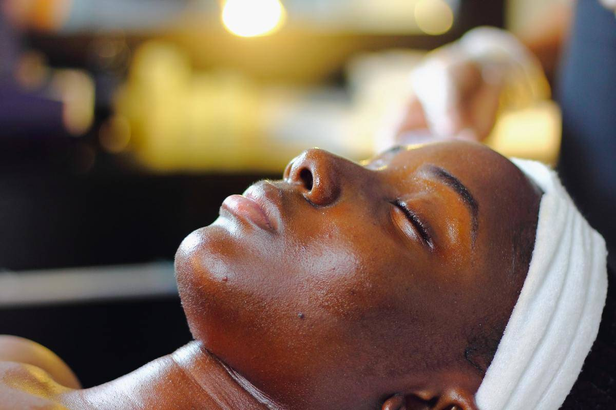 A woman wearing a head wrap lies on an acupuncture table.