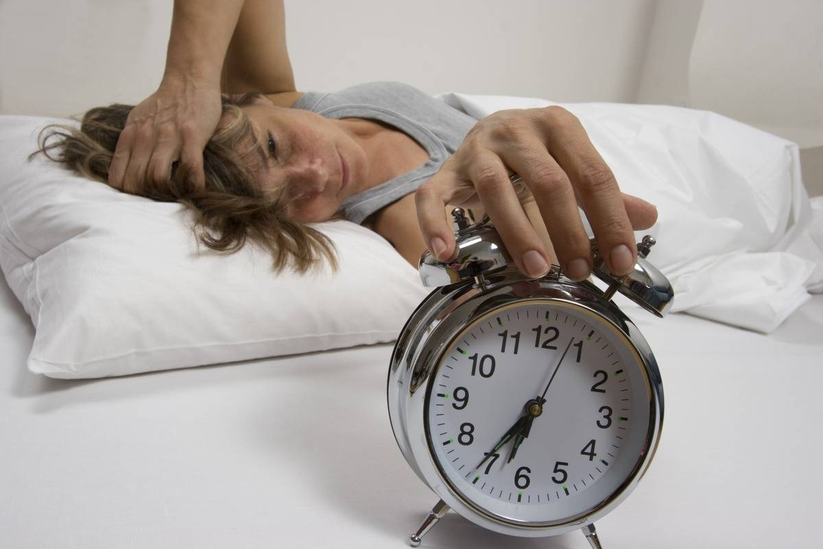 A woman in bed lazily turns off her alarm clock.