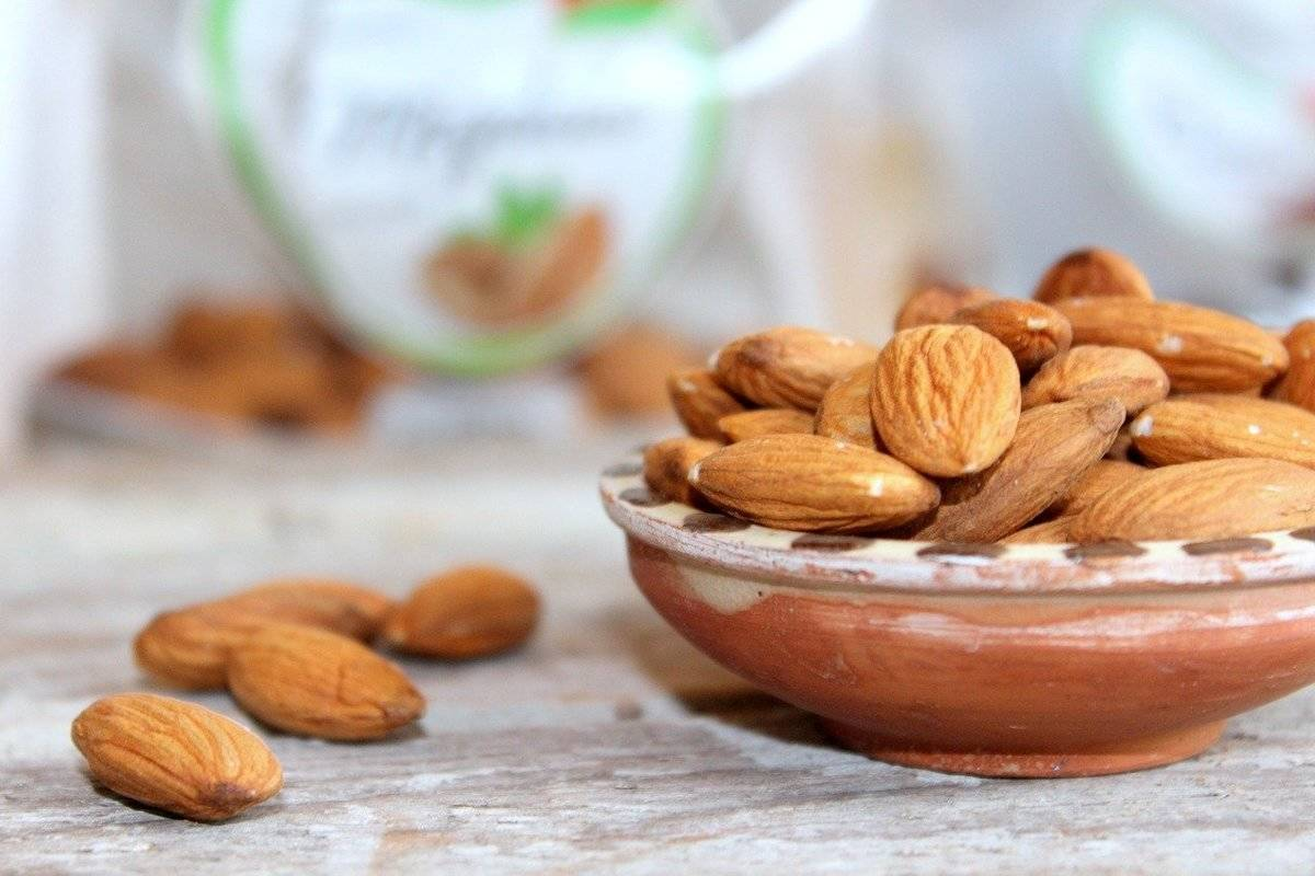 Almonds spill out of a bowl.