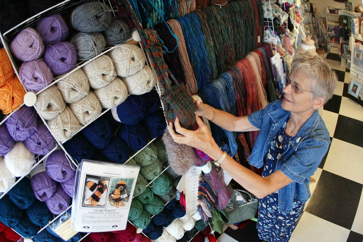 An elderly woman arranges yarn at a shop where she works.