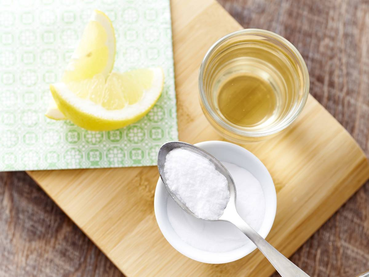 A spoonful of baking soda sits next to a glass fo water and a slice of lemon.