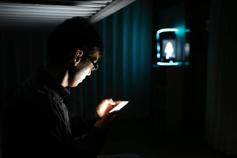 A man scrolls through his cell phone in the dark.