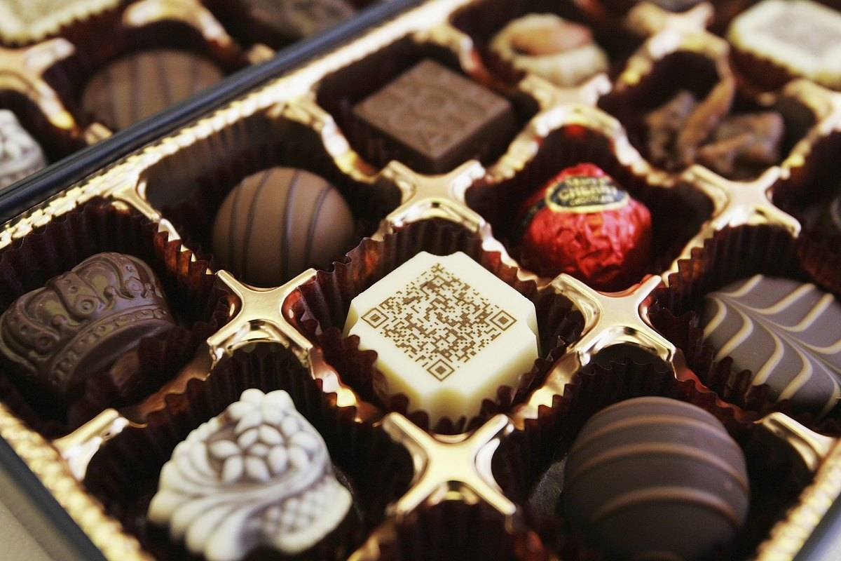 Decorated chocolates are arranged in a box.