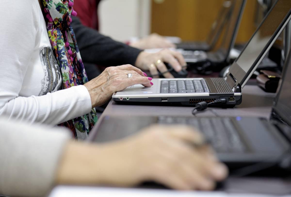 Several seniors type on laptops.