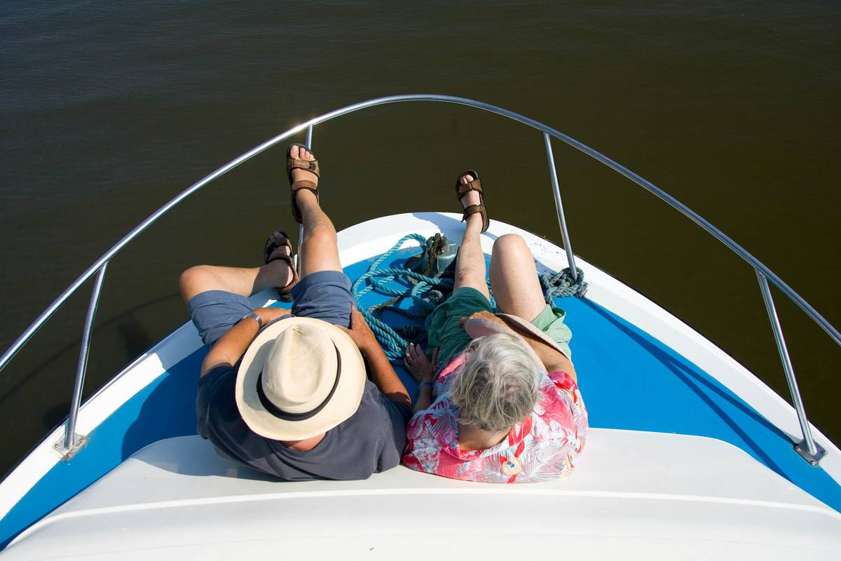 An elderly couple sits on a cruise.