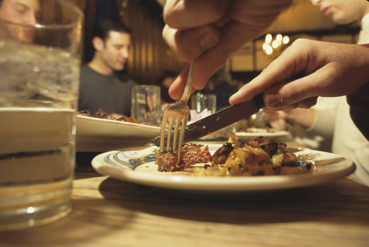 A person cuts steak at a dinner table.