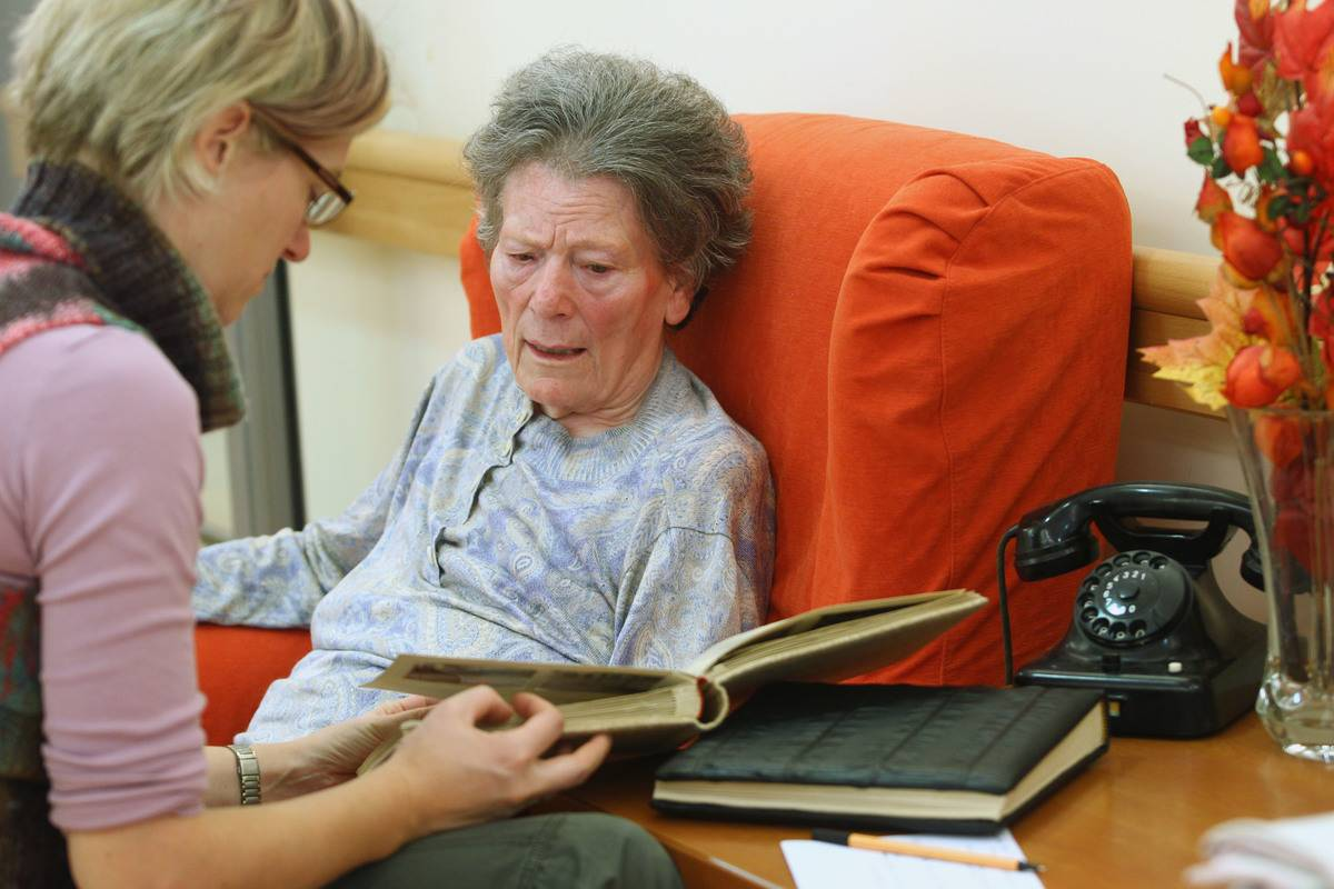 A therapist looks through a photo album with an elderly woman with dementia.