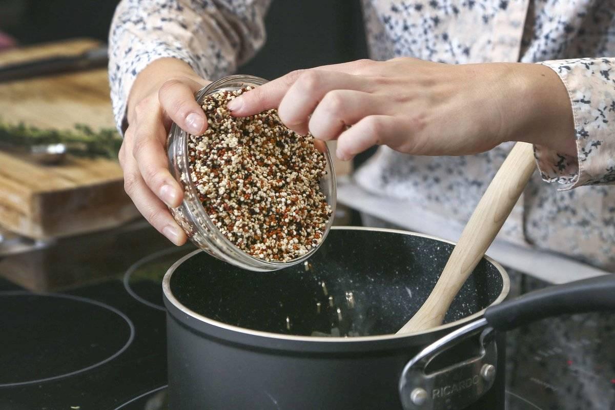 A chef pours dried quinoa into a pot.