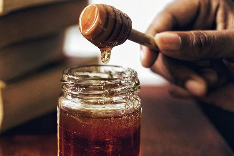 Honey drips off of a honeycomb into a glass jar.