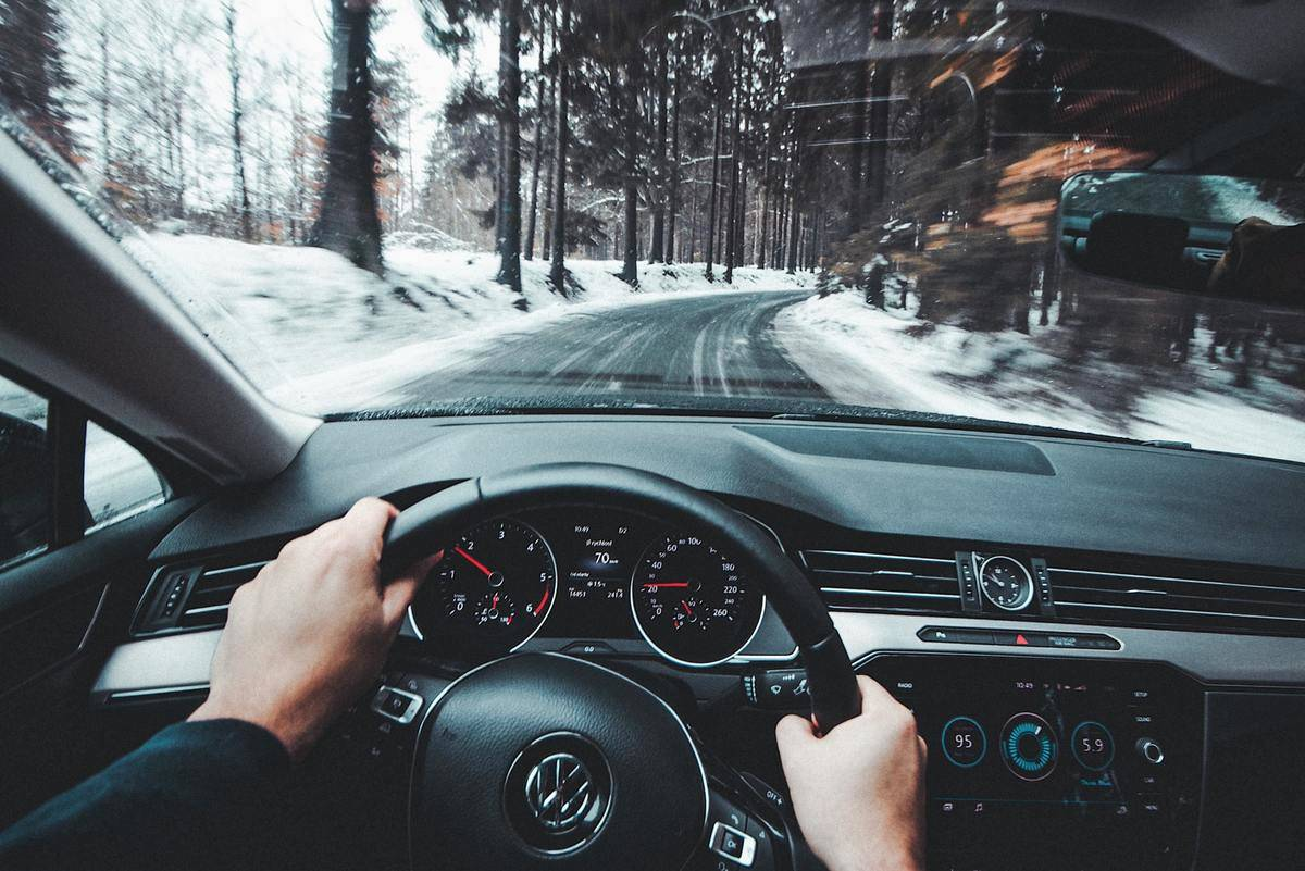A person drives down a snowy road.