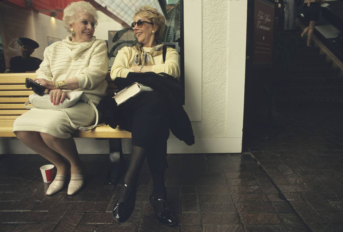 Two elderly women take a break from shopping and chat on a bench.