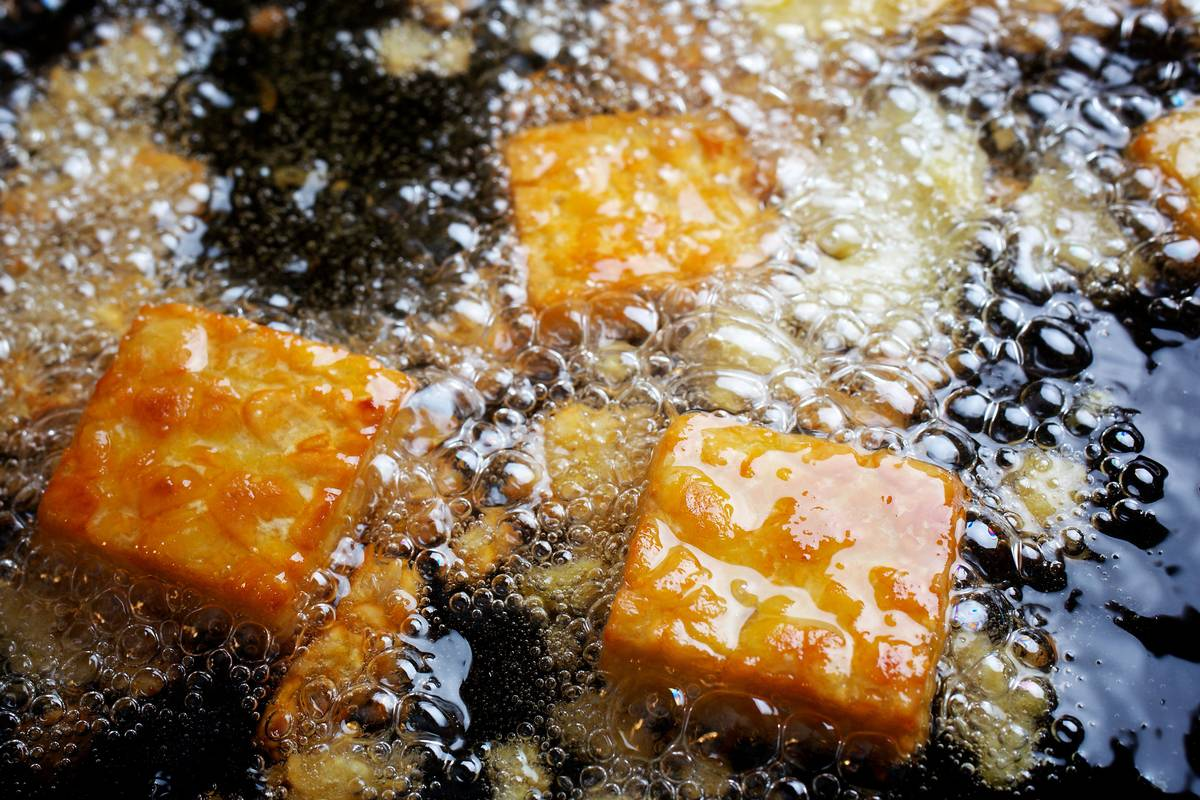 Squares of tempeh cook in oil.