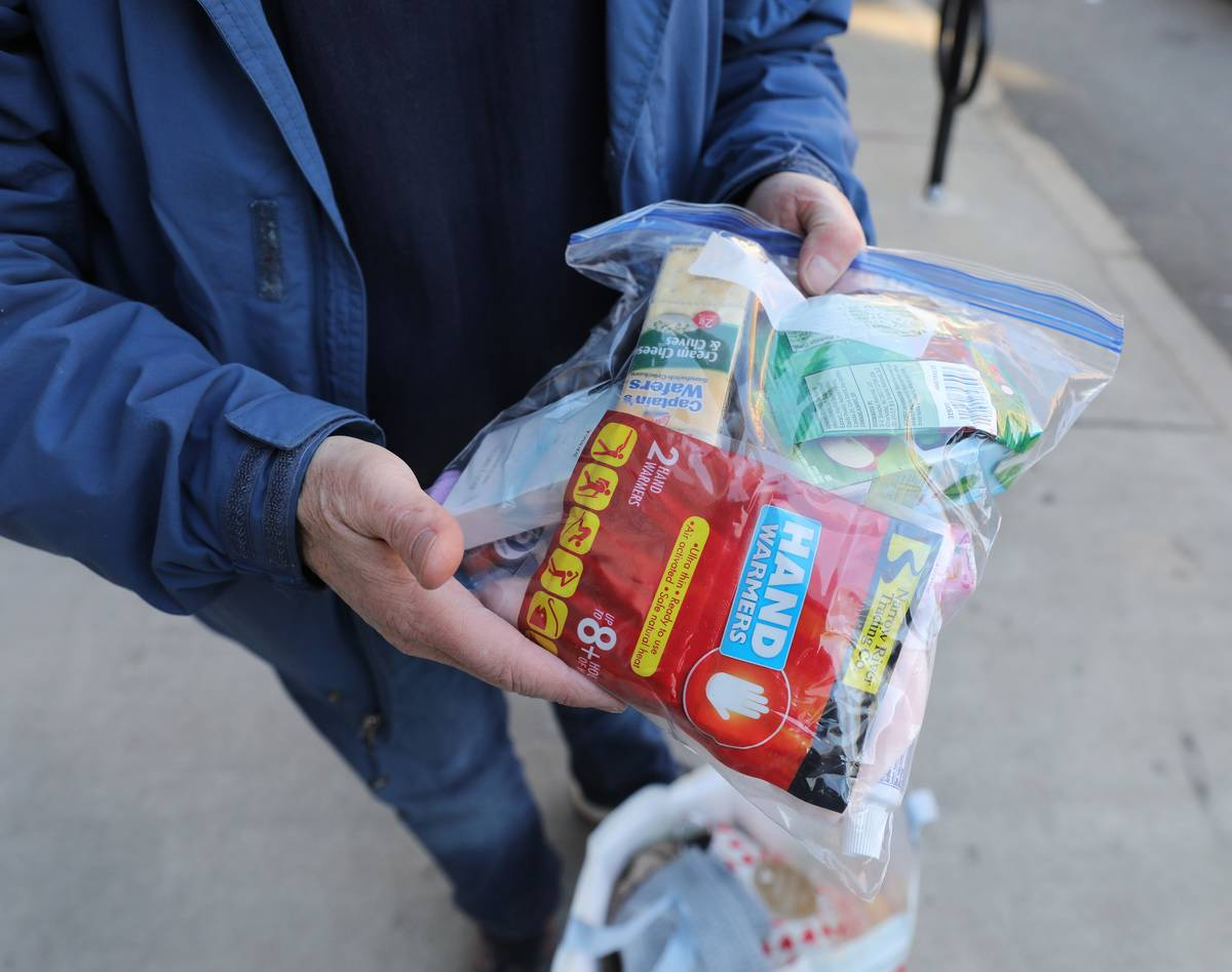 A man holds a bag filled with toiletries and disposable hand warmers.