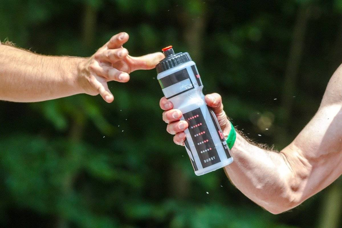 A man hands a water bottle to another person who reaches for it.