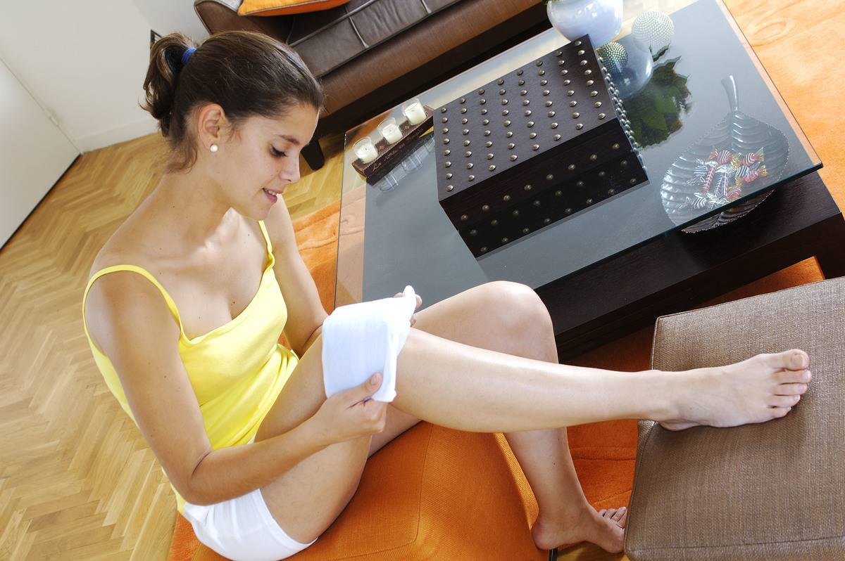 A woman applies a heated pad to her knee.