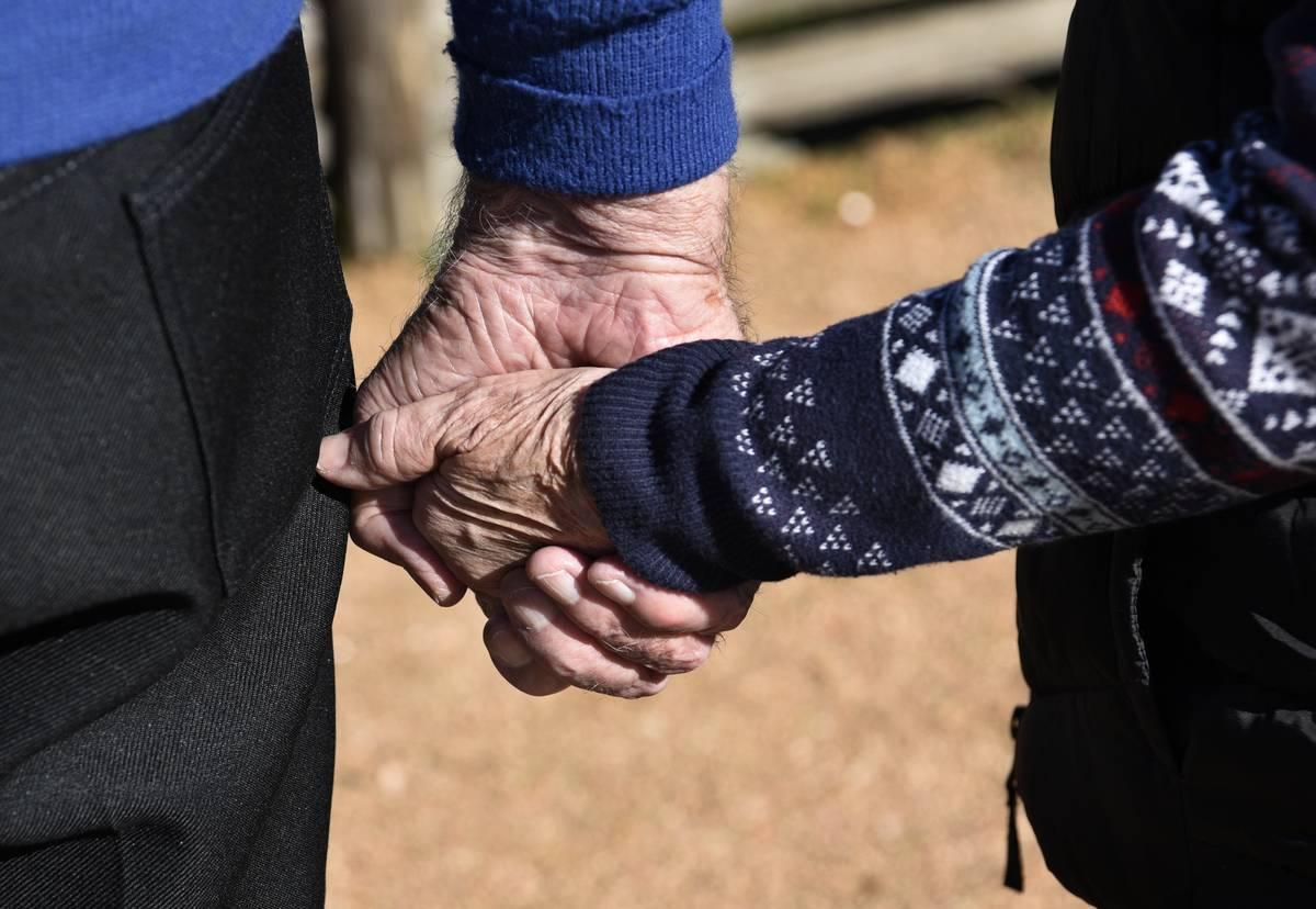 A senior couple walks hand-in-hand.