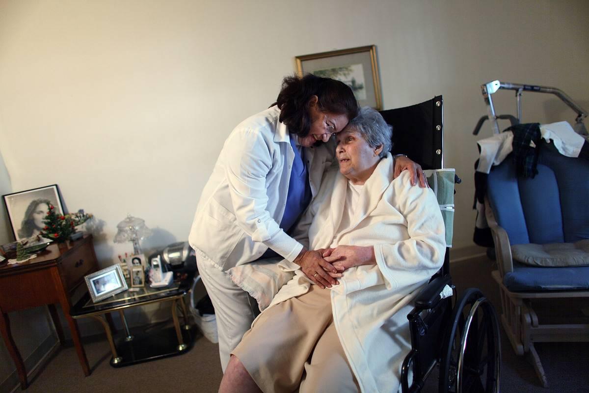 An elderly aid hugs a senior woman during home care.