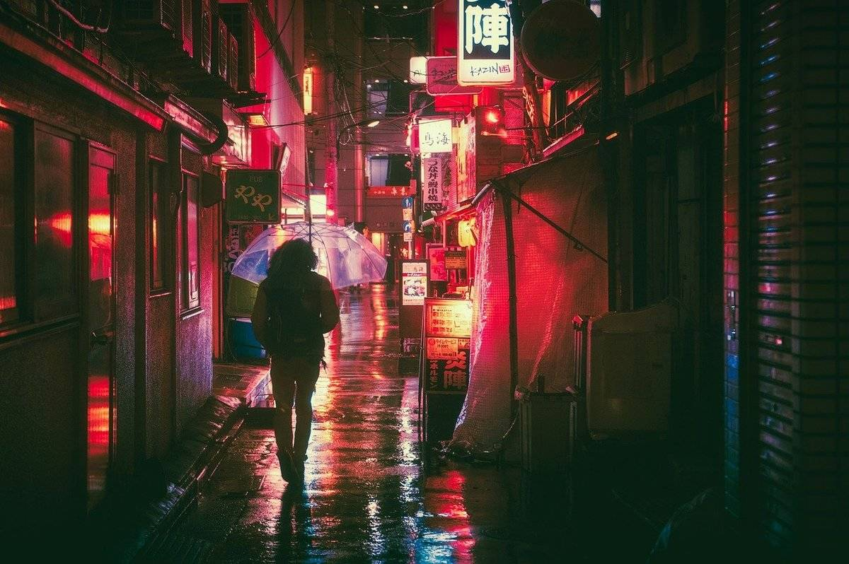 A woman walks through an alleyway in Japan with an umbrella.