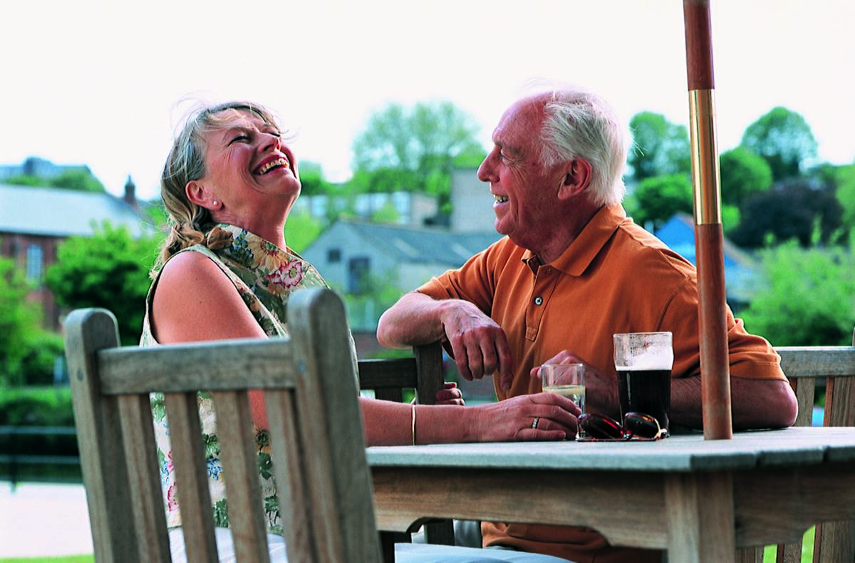 An elderly couple sits outside and chats.