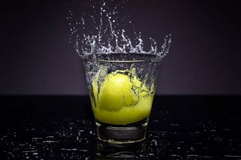 A full lemon drops into a glass of water.