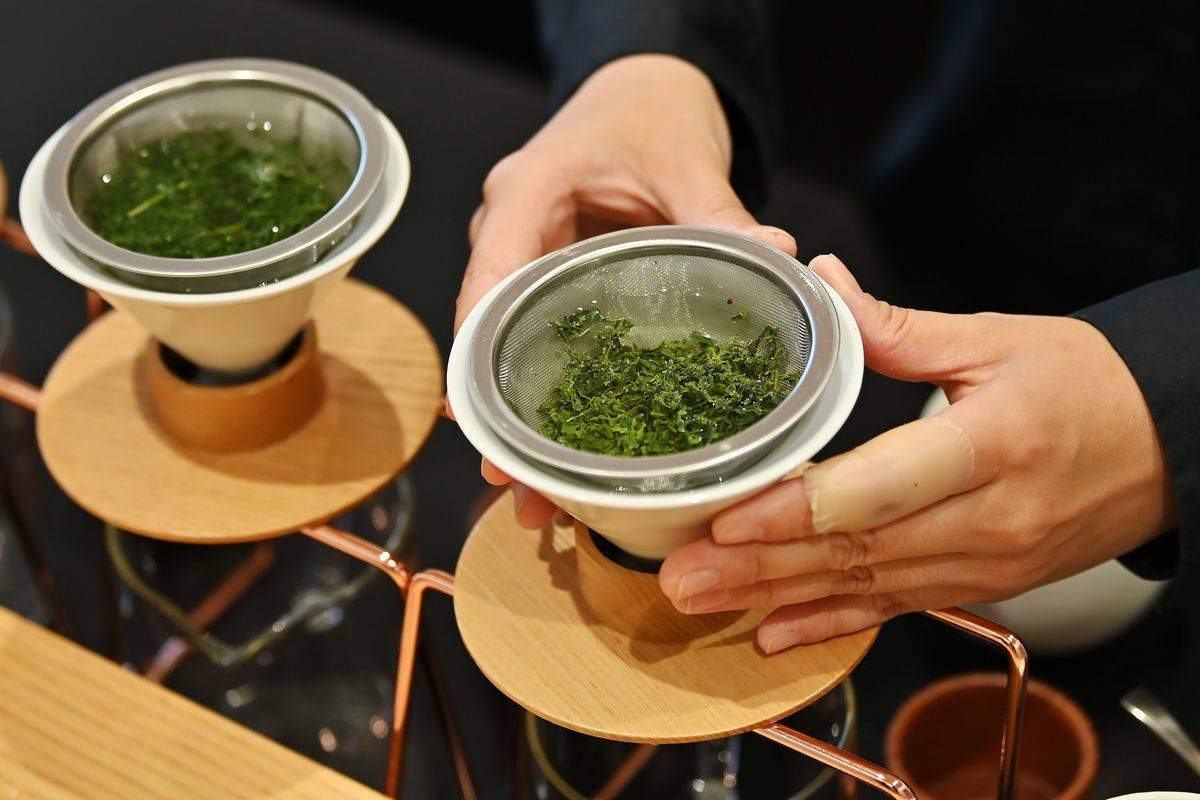 A woman strains green tea leaves in Japan.