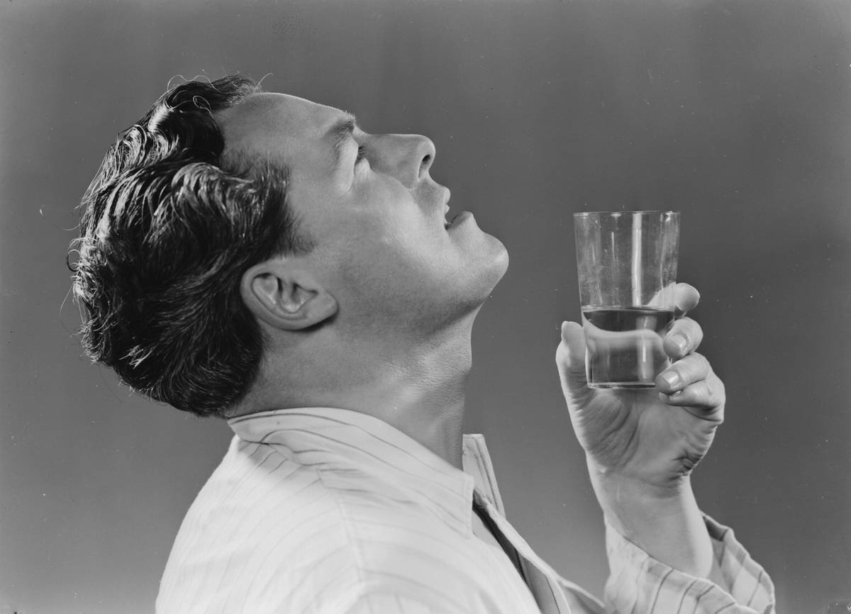 In this 1951 photo, a man gargles water while holding a glass.