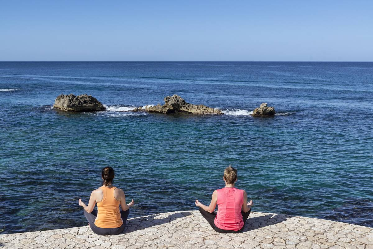 Two women meditate by the sea.
